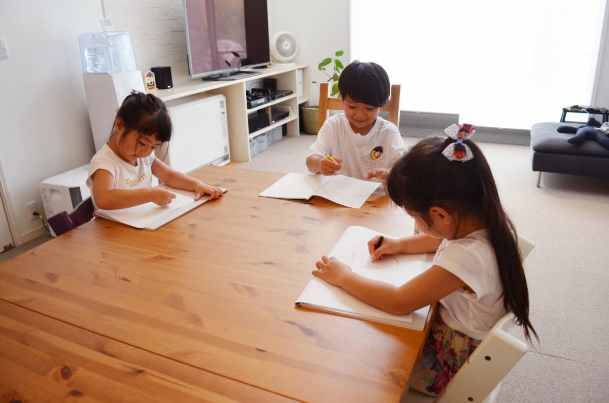 リビングで学習をする子供たち。小学生は宿題をして、幼稚園児はお絵かきをしています。