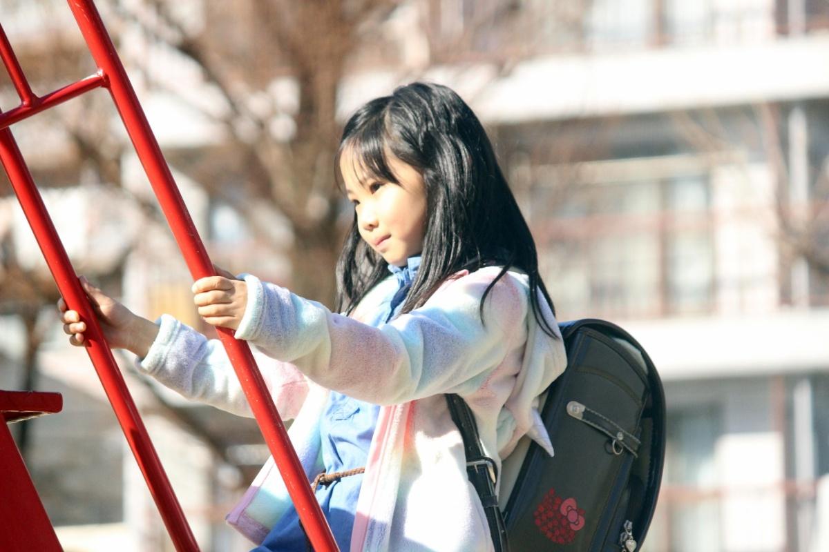 ランドセルを背負って公園で遊ぶ女の子